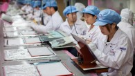 Workers assemble and perform quality control checks on MacBook Pro display enclosures at an Apple supplier facility in Shanghai.
